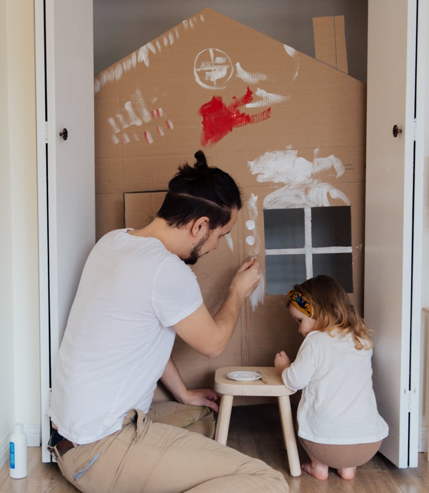 man in white t shirt and brown pants painting cardboard house